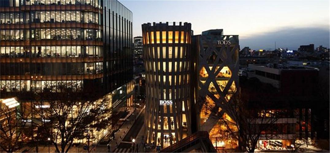 """来自事务所的描述:位于东京表参道大道与窄巷九十度转角的一处八层商业大厦,由伊东丰雄设计的表参道L形大楼围绕。过去建筑的前立面仅面对东京表参道,故侧面对着窄巷就像背部一样不起眼。因此设计想要改变原来与Tod大厦的联系影响,通过一个不规则的圆弧外形实现对角线关系。这是为了放大街角房屋的特征,并强调相邻Tod大厦的内部垂直立面,营造一个明确的""""共生""""效果。建筑结构是钢筋混凝土的多层叶型塔。塔的木质纹理通过水泥浇注木模制成。 © Kozo Takayama Courtesy o"""