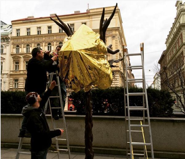 艾未未发布在Instagram上的一张照片。他正在用难民使用的金色保温毯包裹自己的作品《十二生肖头像》。 艾未未似乎从这些金色反光保温毯当中获得了无尽的灵感。本月早些时候,他在布拉格用这些毯子包裹了自己的《十二生肖头像》(Zodiac Heads)。这些作品被安放在国家美术馆的交易大厅(National Gallerys Trade Fair Palace),是这个美术馆成立220周年纪念展览的展品之一。