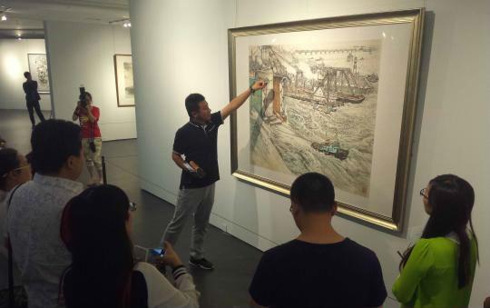 山东美术馆策展人张膑向参观者介绍画作。 胡健 摄