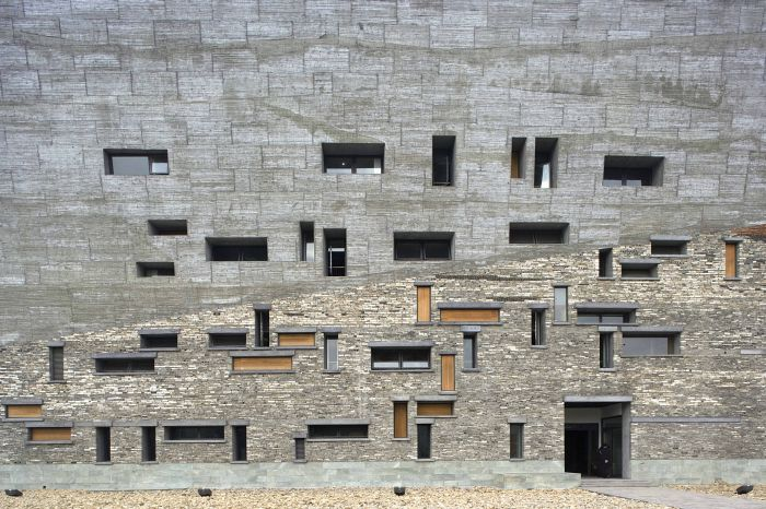 """宁波历史博物馆 宁波历史博物馆在外观设计上大量地运用了宁波旧城改造中积累下来的旧砖瓦、陶片,形成了24米高的""""瓦爿墙"""",同时还运用具有江南特色的毛竹制成特殊模板清水混凝土墙,毛竹随意开裂后形成的肌理效果清晰地显现。王澍这样谈到自己的设计初衷:""""使用'瓦爿墙',大量使用回收材料,节约了资源,体现了循环建造这一中国传统美德,一方面除了能体现宁波地域的传统建造体系、其质感和色彩完全融入自然外,另一意义在于对时间的保存,回收的旧砖瓦,承载着几百年的历史,"""