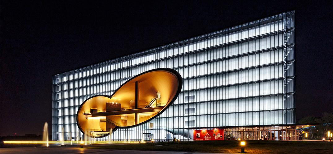 """扎哈·哈迪德设计的凌空SOHO具有未来感的流线外形。  由安藤忠雄设计的嘉定保利大剧院(夜景图),清水混凝土是其标志。  武康路210号是一座典型的西班牙式花园住宅。圆形拱门上方那一处弧形转角曾被上海作家陈丹燕写入《上海的风花雪月》,成为传说中""""罗密欧的阳台""""。 1933年落成的具有强烈时代感的大光明大戏院;1934年,几乎是上世纪30年代美国摩天楼翻版的高达83."""