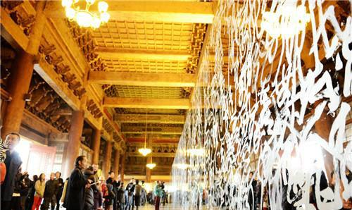 作者:王冬龄 作品名称:大型镜面壁书《易经》 尺寸:32×3.5m 材质:由白色油漆在不锈钢板面上书写而成
