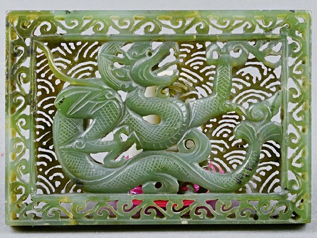 透雕龙纹碧玉带板,呈长方形,正面浮雕三爪龙,以透雕波浪纹作底,龙双角